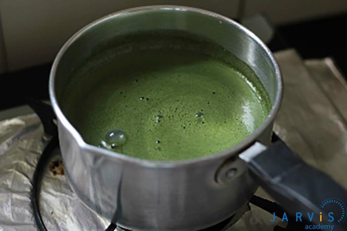 khi nước sôi lăn tăn thì đổ thêm phầ trà xanh vào khuấy đều