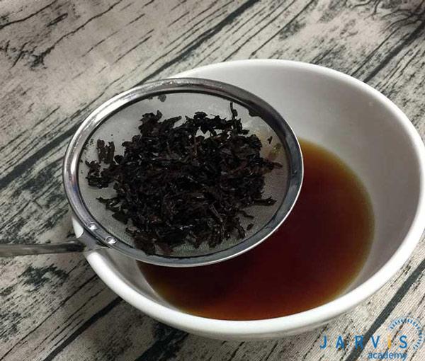 Lọc trà qua rây để lấy bã chè ra